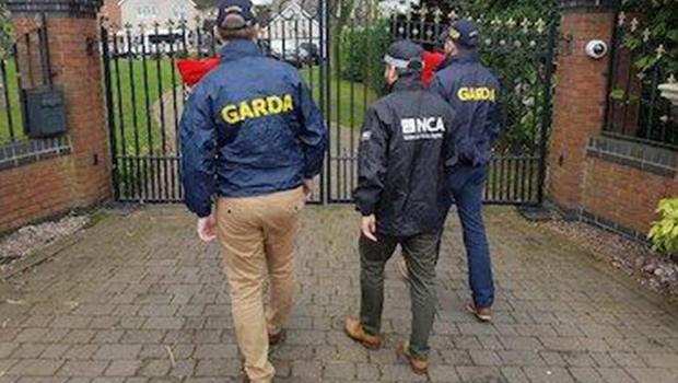 CRIME CALL: Gardai and NCA officers at the house in Tamworth