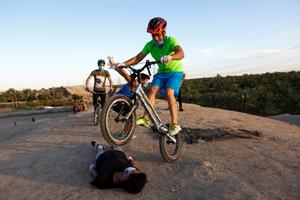 Youths wearing protective face masks use bicycles as they practice parkour, following the outbreak of the coronavirus disease (COVID-19), during the holy month of Ramadan in the holy city of Najaf, Iraq May 3, 2020. REUTERS/Alaa al-Marjani