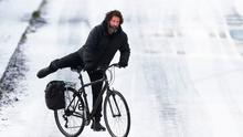 A man cycles in snow (stock photo). Photo: Niall Carson/ PA