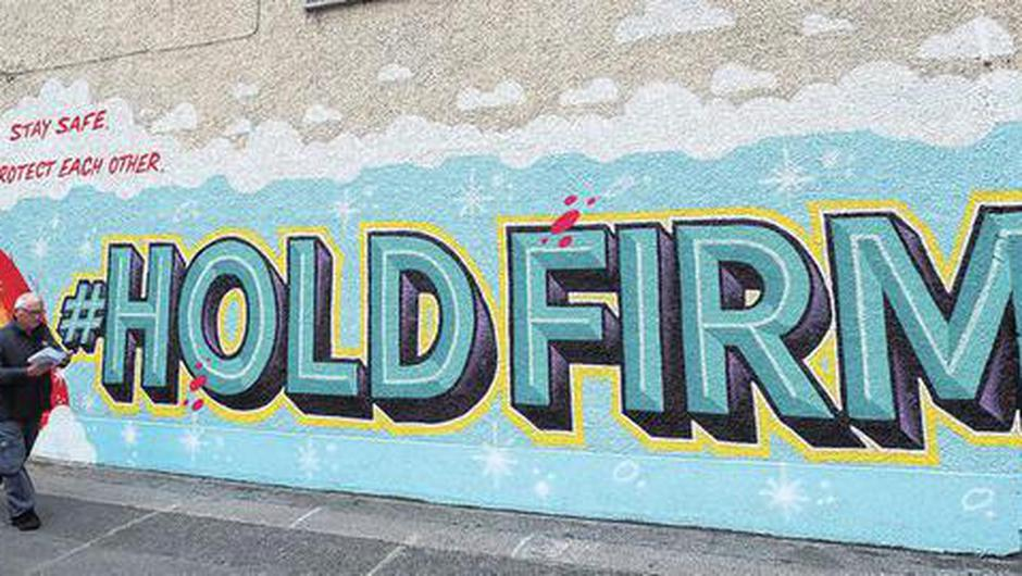 A postman walks past a Dublin mural inspired by the HSE 'Hold Firm' campaign. Photo: Brian Lawless/PA