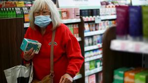 A woman wearing a protective face mask is seen in a shop, in London. People who are over-70 and are vaccinated in Ireland can go shopping but must wear a face mask. (Reuters)