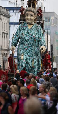 Crowds watch as performers from the French arts group Royal de Luxe take to the streets of Limerick with their giant grandmother parade. Photo: PA