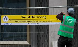 A Covid 19 compliance officer puts up social distancing signs on a building site in Dublin's city centre. Photo:Gareth Chaney/Collins