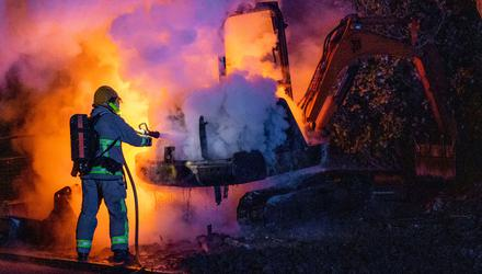 A firefighter extinguishes a JCB digger which was set alight in Derry City. Photo: PA