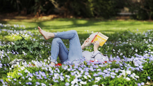 Moment's pause: A woman reads her book among some flowers on a spring day in the Botanic Gardens, Dublin. Photo: Leon Farrell/Rollingnews.ie