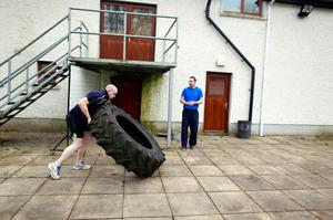 Fr Pierre Pepper turns over a tractor tyre during training. Photo: PA