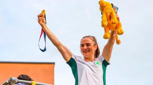 Kellie Harrington displays her Olympic gold boxing medal from an open-top bus near her home on Dublin's Portland Row. Picture: PA