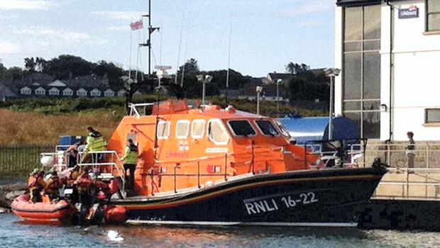 Baltimore lifeboat crew carring the remains of Douglas Perrin to shore after his body was found