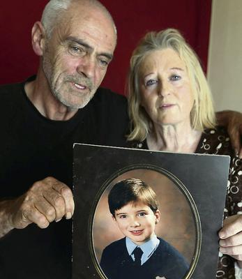 Larry and Elizabeth Johnson, parents of Dean Johnson, with a photo of him as a boy.