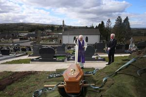 THE LOVED ONE: Parish Priest Gerard Alwill and undertaker Pat Blake at the graveside at St Ninnidh's cemetery in Derrylin, during the burial of Fermanagh's first Covid-19 victim, 72-year-old Anne Best. Photo: John McVitty