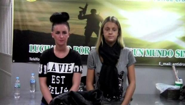 Michaella McCollum and Scotswoman Melissa Reid stand as they are questioned by police in Lima airport in 2013