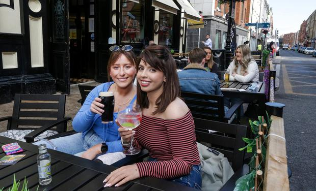 Happy customers Shauna Brennan and Kerrie Murphy, enjoy their first drinks outside Slatterys pub on Capel Street. Picture; Gerry Mooney