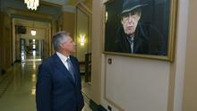 Northern Ireland First Minister Peter Robinson stands in front of a portrait of the late Ian Paisley located in the Great Hall at Stormont in Belfast yesterday. Photo: Getty