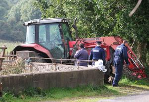 An inspector from the Health and Safety Authority and a garda forensic technician examine the tractor at the scene of a tragedy in which a man lost his life in a farm accident.