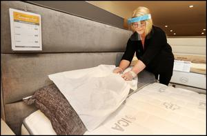 New normal: EZ Living store manager in Tallaght, Dublin, Pauline Cooke places a disposable protection sheet on a bed prior to it being tested. Photo: Steve Humphreys