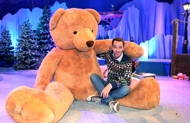Grin and bear it: Ryan Tubridy and a giant furry friend on the set of The Late Late Toy Show Photo: Steve Humphreys