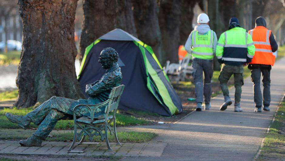 Builders walk past the tents of homeless people in Dublin city centre