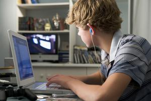 Boy in bedroom using laptop and listening to MP3 player