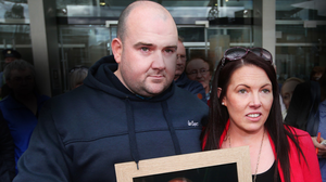 Bobby Ryan's children Robert and Michelle hold a photo of their murdered father outside court. Picture: Steve Humphreys