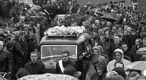 Mourners line the streets near St Mary's Church to watch the funeral procession of the 13 people who died on Bloody Sunday in 1972