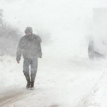 A man walks on the Carnlough to Ballymena road in Co Antrim after abandoning his vehicle due to snow