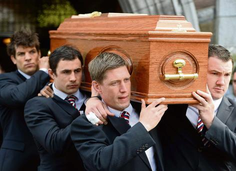 Members of the Munster Rugby team with the coffin at the Church.