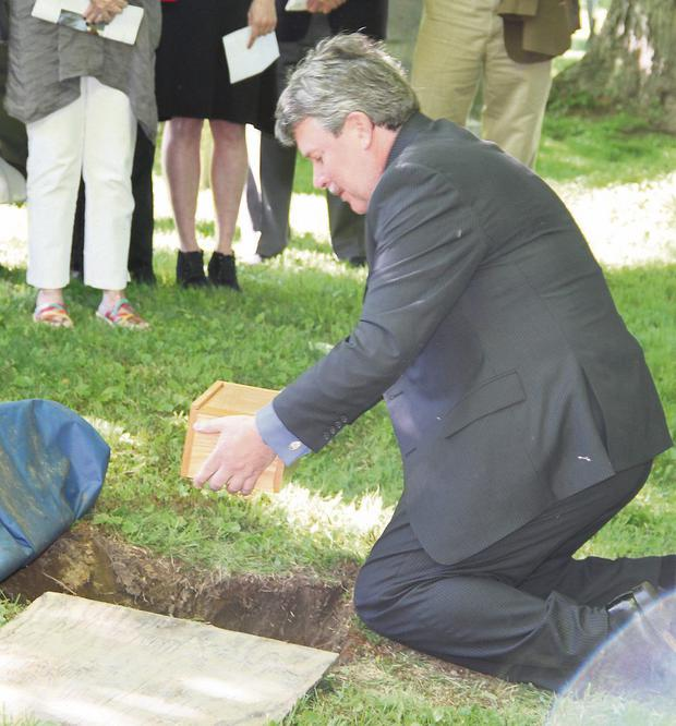 Vincent's son Cian places the remains in the ground