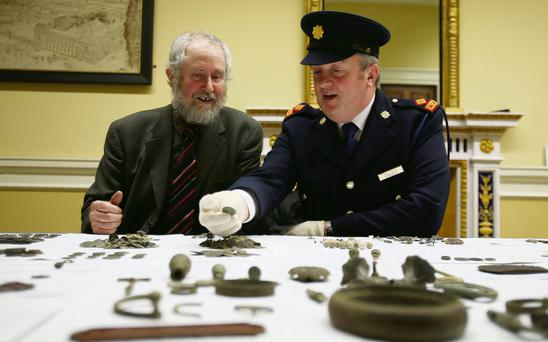 Ned Kelly, keeper of antiquities at the National Museum of Ireland (left), and Garda Superintendent David Taylor view some of the 900 artefacts illegally looted in Ireland, including silver coins from the Middle Ages