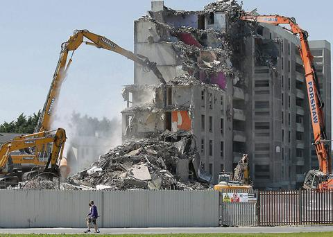 Demolition machines dismantle tower block 8 on Sillouge Road in Ballymun