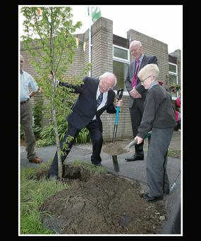President Higgins plants a tree with help from Ryan Dolan (8) as St Joseph's principal Niall Desmond looks on.