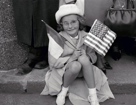 Flag day: Margaret Murphy waits patiently at Dublin Airport to welcome JFK on his historic visit to Ireland.