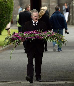 A mourner carries a wreath