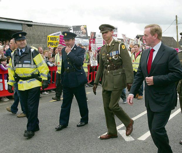 Taoiseach Enda Kenny (right) runs the gauntlet of pro-life protesters in Ballinalee, Co Longford