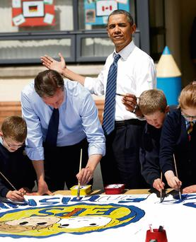 Barack Obama reacts as the sun comes out as he works alongside David Cameron and students on a school project about the G8 summit