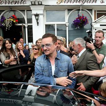 Bono leaves Finnegan's Pub in Dalkey where he had lunch with the US First Lady Michelle Obama
