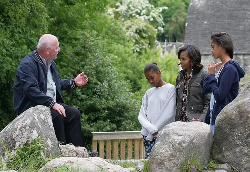 Glendalough Tour guide George McClafferty talks to theFirst Lady of the United States, Michelle Obama and her daughters Sasha and Malia about fable of the Deer Stone, during the Obama family tour of the Glendalough Monastic site in the Wicklow mountains National park yesterday