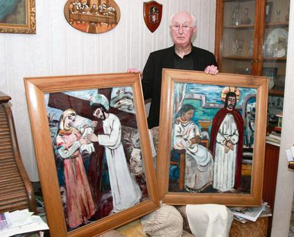 Fr Martin McNamara with two of the remaining eight paintings at St Peter and St Paul Church in Kiltullagh, Co Galway, after a gang stole six others