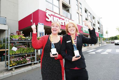 Aisling Butler and Laura Maher, from Reilly's SuperValu in Sallins, Co Kildare, prepare to crack open the champagne amid rumours - which later proved to be incorrect - that the shop had sold the winning ticket