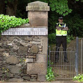A police officer stands at the entrance to Corstorphine Hill in Edinburgh after the woman's remains were found in a shallow grave