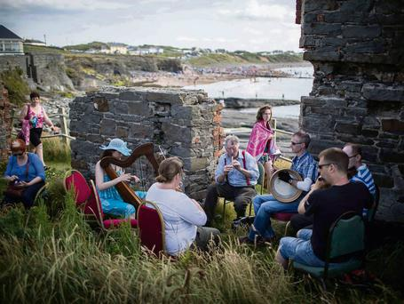 Musicians take part in an impromptu session beside the beach at Spanish Point