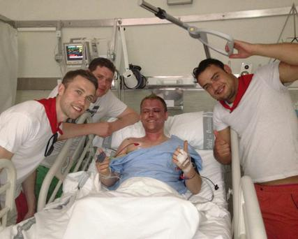 Robert Thackaberry in hospital surrounded by friends after crushed by a bull