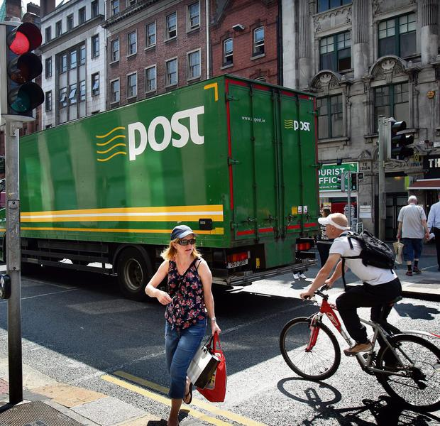 A a woman evades a cyclist breaking the red light at College Green, Dublin