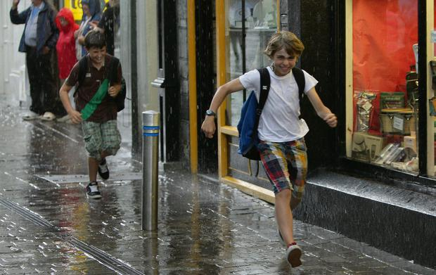 Running for cover: Two boys race to take shelter from a downpour in Galway city