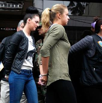 Police escort Michaella McCollum (left) and Melissa Reid (right) in handcuffs as they are moved from the National Police anti-drug headquarters to a court in Lima, Peru.