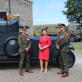 Lieutenant General Conor O'Boyle, Helen Collins and Colonel Brian Reade stand beside the armoured car, which Michael Collins had travelled in the day he was shot