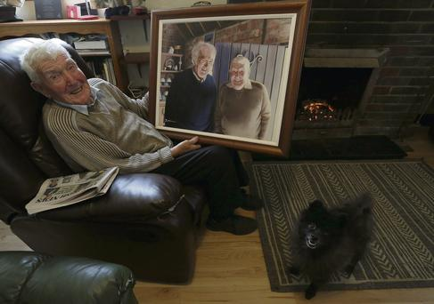 Blacksmith Barney Devlin (95) in his home in Castledawson, Co Derry, with a painting of him and Seamus Heaney at the forge that inspired the poet to write the poem of that name.