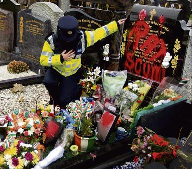 A garda at Ryan's grave, above, which was defaced with graffiti reading 'Rat Scum'