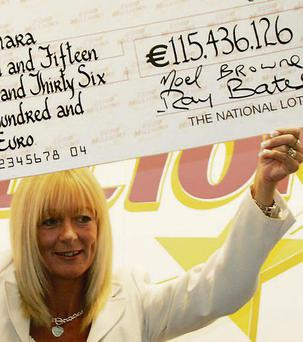 Dolores McNamara holding up her €115m cheque