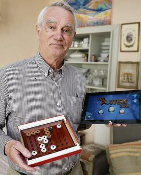 Brian McCarthy at his home with his Power Game board-game and the tablet version