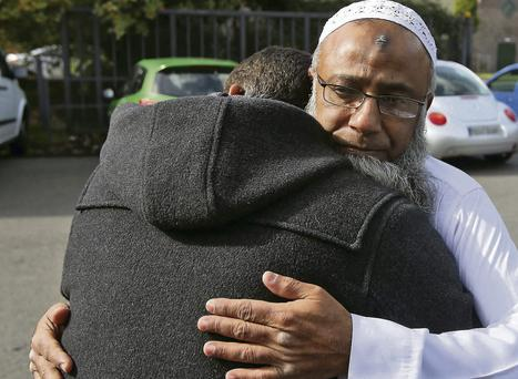 Dr Muhammad Taufiq Sattar is consoled by a friend at the Islamic Dawah Community Centre, Castleknock, Dublin